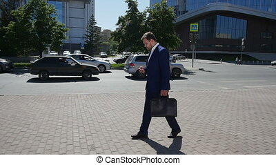 Businessman walking in the street to work. Slow motion