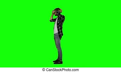 Virtual reality gamer playing with a VR headset. Green...