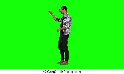 Man wearing virtual reality goggles. Using gestures with hands. Green screen
