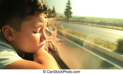 Boy Looking Out Window - Portrait of a sad young boy looking...