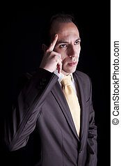 Portrait of a young business man thinking, isolated on black background. Studio shot.