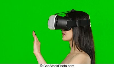 Virtual reality game. Girl with surprise and pleasure uses head-mounted display. Green screen. Close up