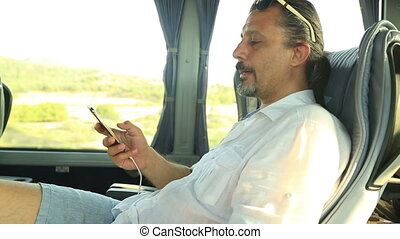 Man talking on the phone in the bus - Passenger using a...