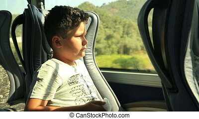 Child on the bus - Portrait of a tired young boy looking out...