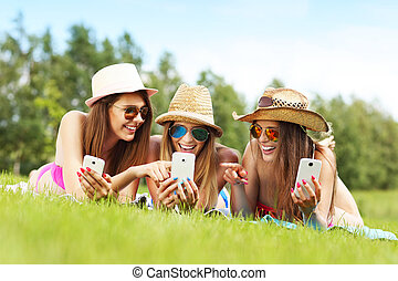 Happy group of friends lying on the grass and texting