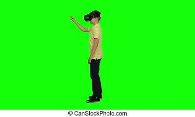 Child using virtual reality headset - the future of entertainment and immersive story telling. Green screen