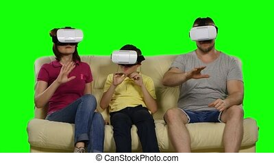 Family using VR glasses sitting on the sofa. Green screen -...