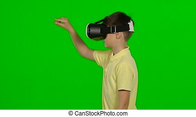 Little boy use virtual reality headset helmet. Green screen...