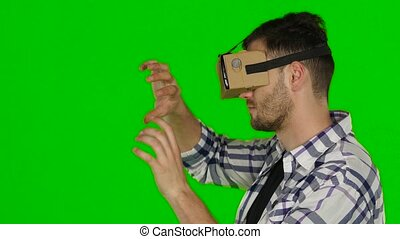 Man wearing virtual reality goggles. Green scree. Close up -...
