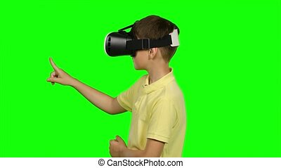 Boy use virtual reality headset helmet. Green screen -...