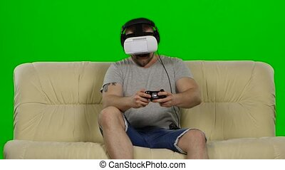 Man wearing virtual reality goggles Studio shot, white couch...