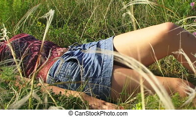 Girl is resting in the meadow