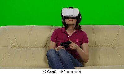 Women in virtual reality glasses on the couch. Green screen