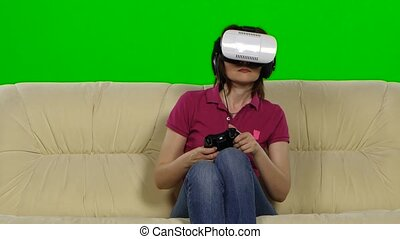 Woman in VR glasses playing game while sitting on sofa at home. Green screen