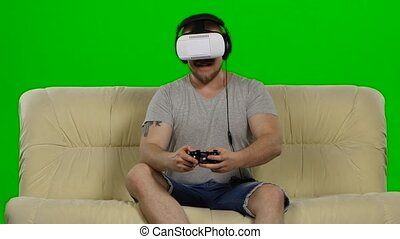 Young handsome man on sofa wearing VR headset glasses. Green screen