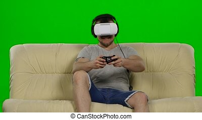 Man in virtual reality glasses Green screen - Young handsome...