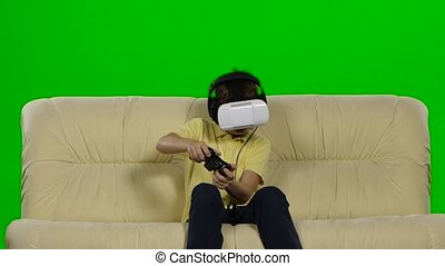 Virtual reality mask. The little boy with surprise and pleasure uses head-mounted display. Green screen