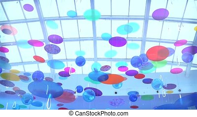 Multicolor discs swinging and rotating under glass roof clip