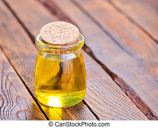 oil in glass bottle - oil in bottle and on the wooden table