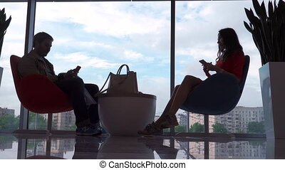 Young woman and man sitting and using their smartphones...