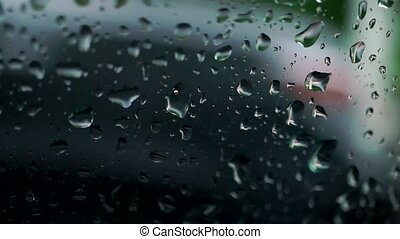 Car passing by behind rainy window. Slow motion bokeh video...