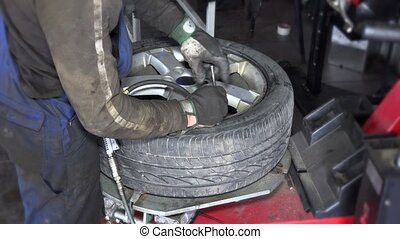 dirty worker hands inflate tire air wit compressor on...