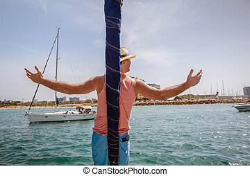 Man standing on a bow of sailboat with arms raised