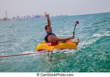 Man sitting in inflatable ring towed by a boat in the water...