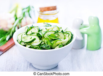 salad with cucumber in the white bowl and on a table