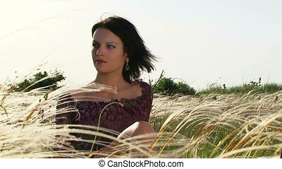 A girl in a field - A beautiful girl sitting in the field...