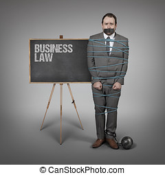 Business Law on blackboard with businessman tied with rope at office
