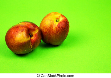 Two fresh nectarines on a bright green background - Two...