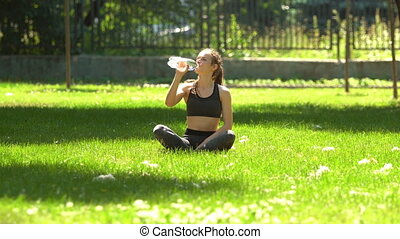 Woman drink water after sport in a city park on green grass