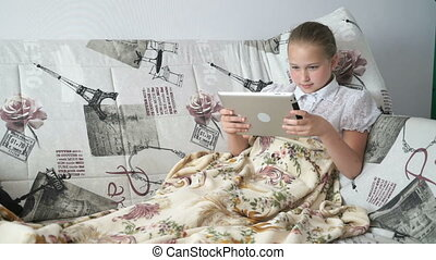 Teenager girl lying on a bed with a digital tablet