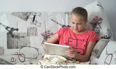 Child lying on the bed with a digital tablet - Child lying...