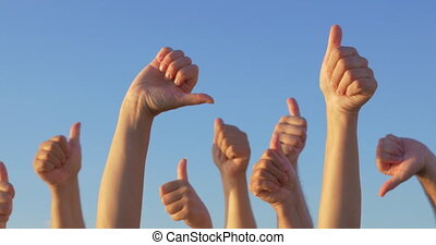 Disagreement in voting - Hands raised with thumbs-up and...