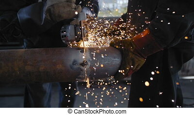 Worker Cutting Steel Pipe with Angle Grinder