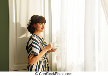 Girl drinking coffee by the window - Pretty girl drinking...
