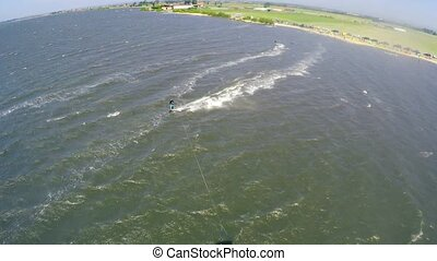 Aerial kite view of kitesurfer gliding across river on a...