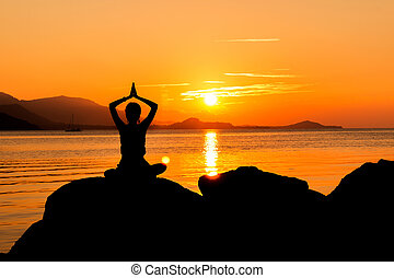 Silhouette of young woman practicing yoga on the beach sunset background