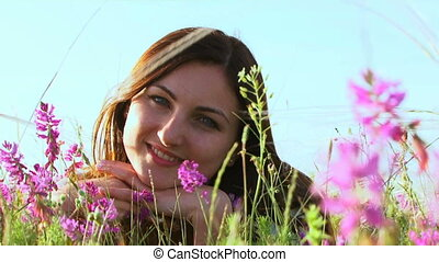 Girl in the field against the sky - She lies on the field of...