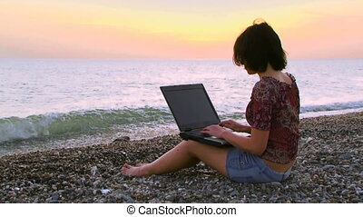 Girl with a laptop on the sea