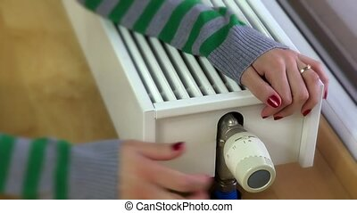 girl warming hands on modern radiator at home. Heating...
