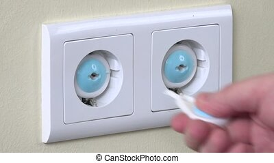 Hand remove safety plug from electricity outlet and insert...