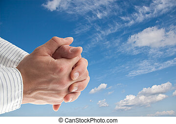 praying hand in front of a blue sky - blue sky with isolated...