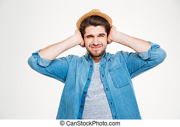 Frowning handsome young man covered ears by hands over white...