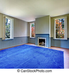 Unfurnished living room with Antique fireplace and blue carpet.