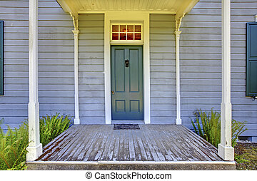 Open entrance porch with columns and blue door of an old...