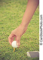 Hand hold golf ball with tee on course, close-up vintage color