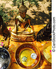white lotus floating on water in golden bowl and Bhudda...